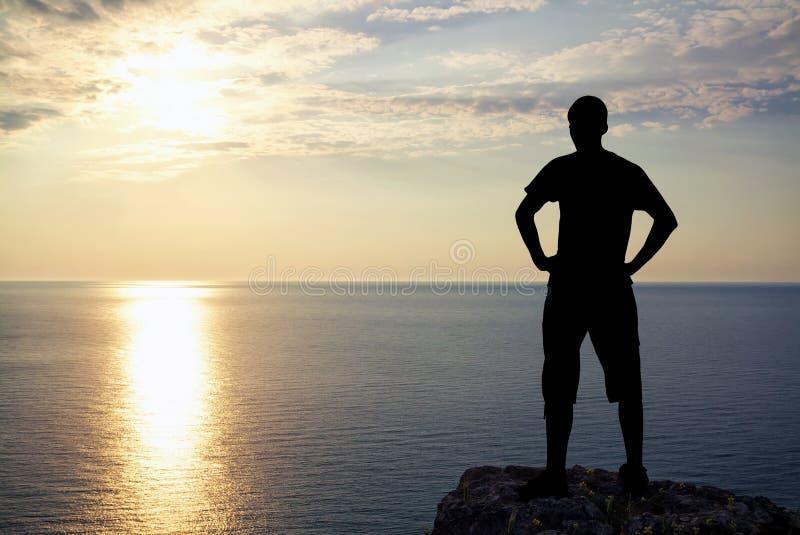 Silueta del hombre en roca en la puesta del sol. foto de archivo libre de regalías