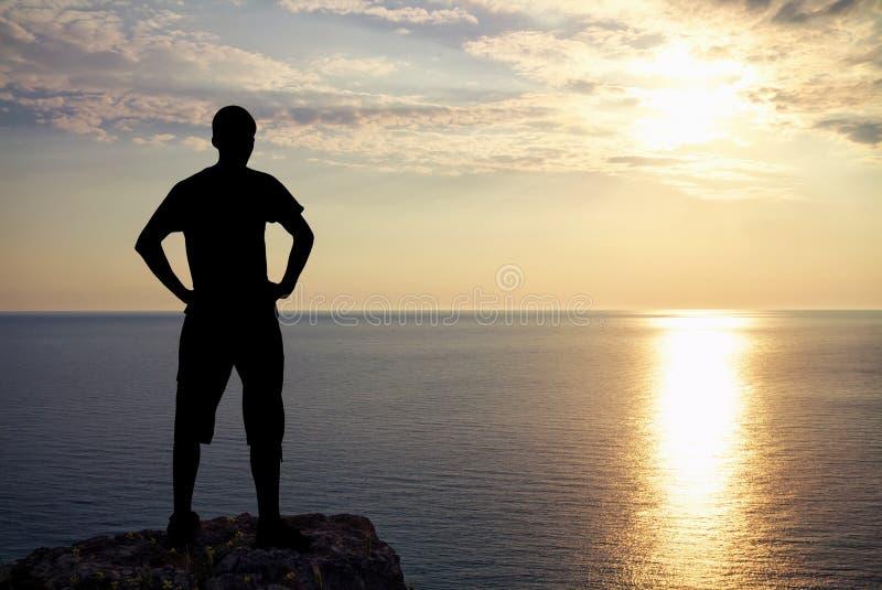 Silueta del hombre en roca en la puesta del sol. Hombre encima de la montaña. imágenes de archivo libres de regalías