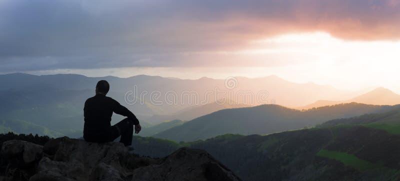 Silueta del hombre en un fondo de la puesta del sol del top de la montaña imágenes de archivo libres de regalías