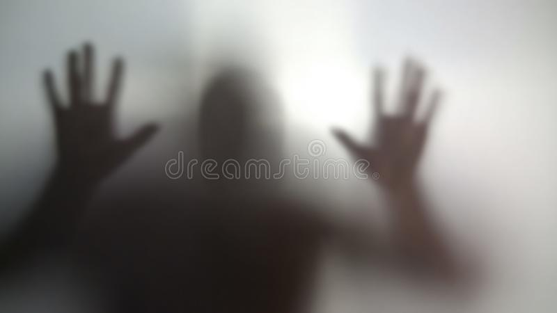 Silueta del hombre enojado contra la pared transparente, esquizofrenia, apego fotografía de archivo libre de regalías