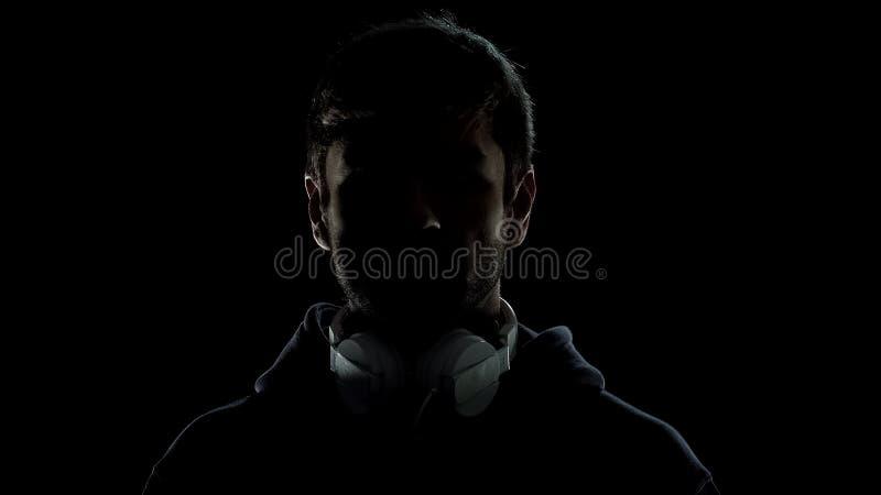 Silueta del hombre joven en auriculares en el fondo negro, generación milenaria fotos de archivo libres de regalías