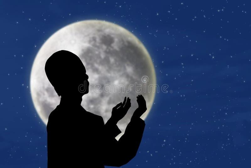 Silueta del hombre musulmán que ruega debajo de la luna azul stock de ilustración