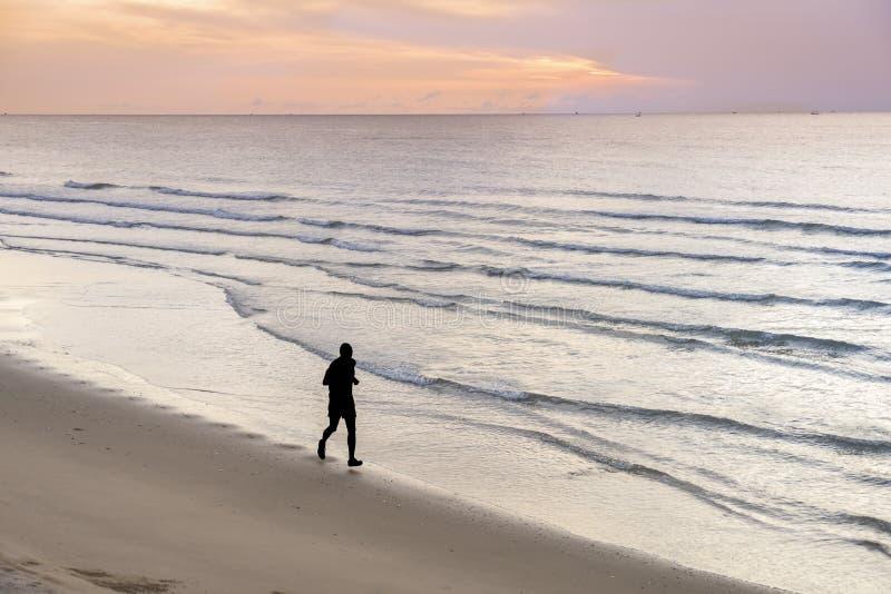 Silueta del hombre que activa en la playa imágenes de archivo libres de regalías