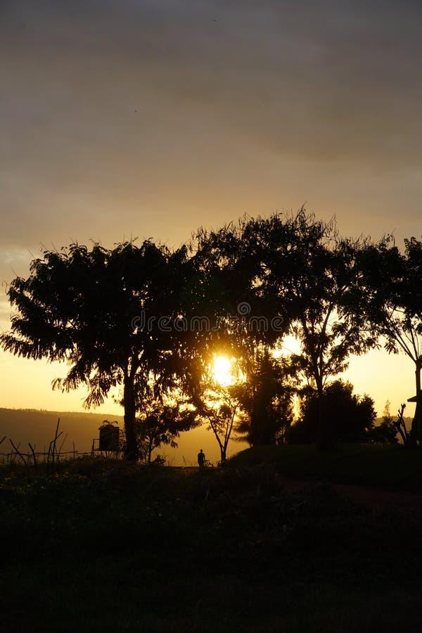 Silueta del hombre que camina hacia puesta del sol imagen de archivo libre de regalías