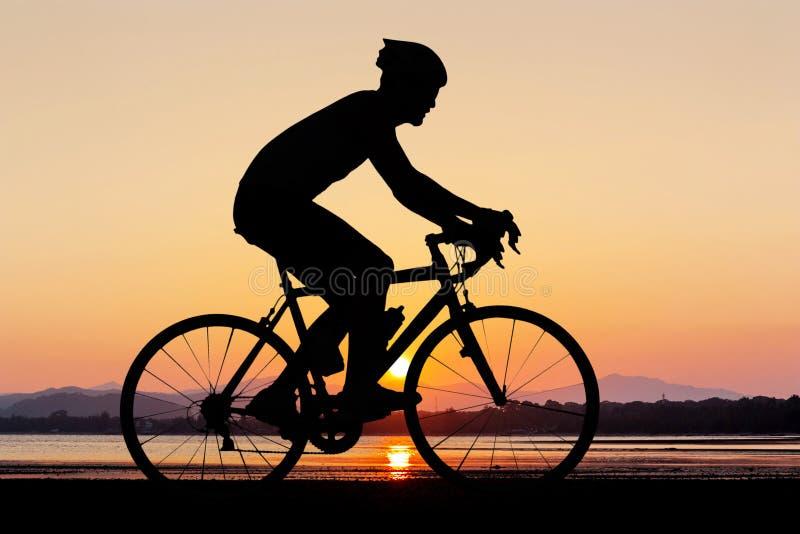 Silueta del hombre que completa un ciclo en la playa fotografía de archivo