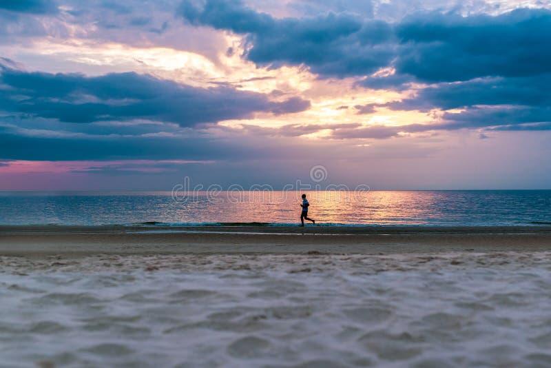 Silueta del hombre que corre en la playa en la puesta del sol foto de archivo libre de regalías