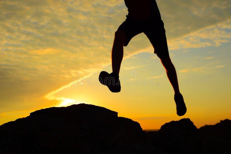 Silueta del hombre que corre en Rocky Trail en la puesta del sol Las piernas se cierran para arriba Deportes extremos fotos de archivo