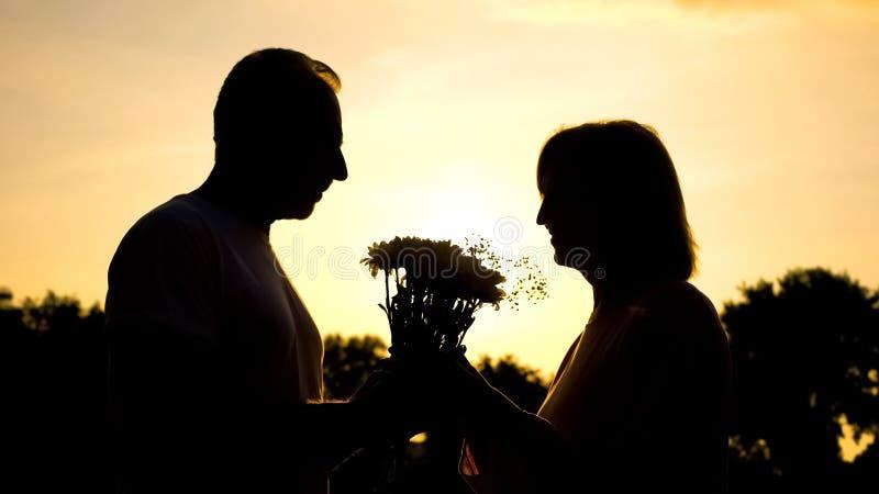 Silueta del hombre que da las flores a la mujer, sorpresa agradable, felicidad de la edad avanzada imágenes de archivo libres de regalías