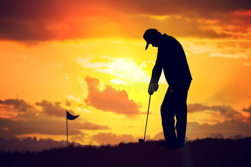 Silueta del hombre que juega a golf en la puesta del sol imagenes de archivo