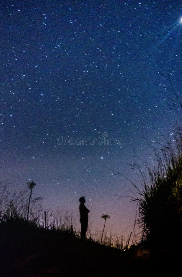 Silueta del hombre que mira el infinito de estrellas foto de archivo