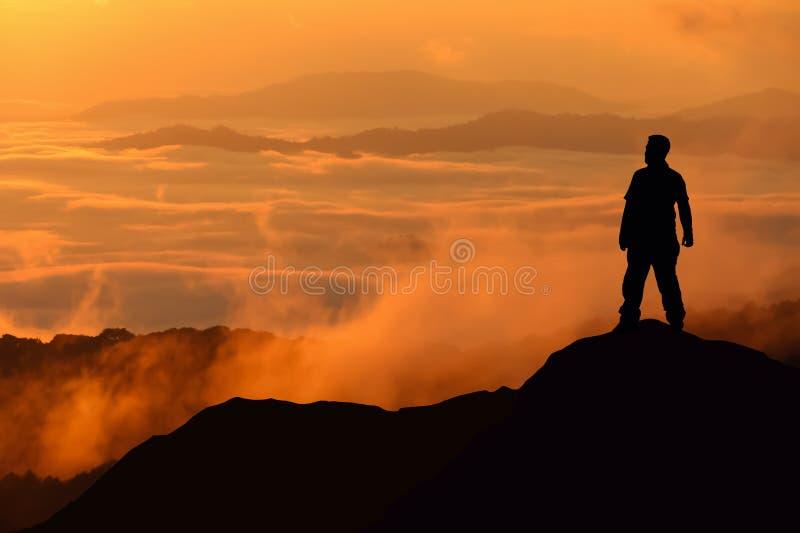 Silueta del hombre que se coloca en el top de la montaña fotografía de archivo