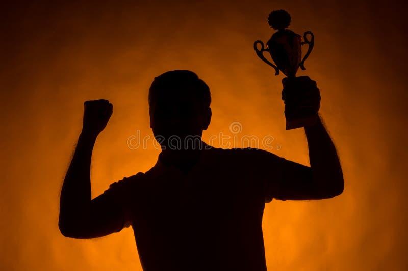 Silueta del hombre que sostiene la taza de campeón fotos de archivo libres de regalías