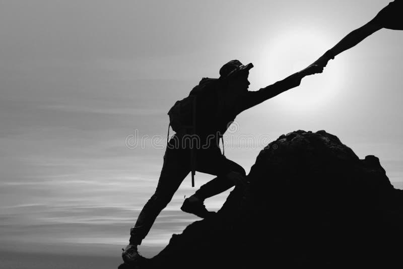 Silueta del hombre que sube para arriba la monta?a con la mano que da ayuda imagen de archivo