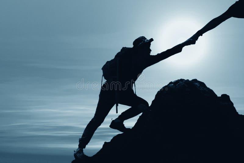 Silueta del hombre que sube para arriba la monta?a con la mano que da ayuda fotografía de archivo libre de regalías