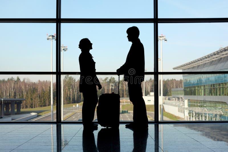 Silueta del hombre y de la muchacha con equipaje fotografía de archivo libre de regalías