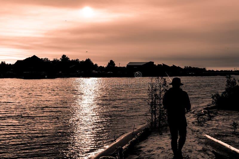 Silueta del individuo en la pesca del sombrero en el río en puesta del sol fotografía de archivo