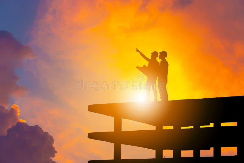 Silueta del ingeniero y del trabajador en el solar, emplazamiento de la obra con la trayectoria de recortes en la puesta del sol  fotos de archivo
