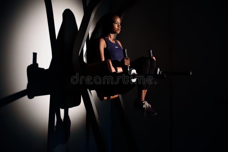 Silueta del instructor afroamericano magnífico joven de la aptitud de la mujer que se resuelve en el gimnasio imagenes de archivo