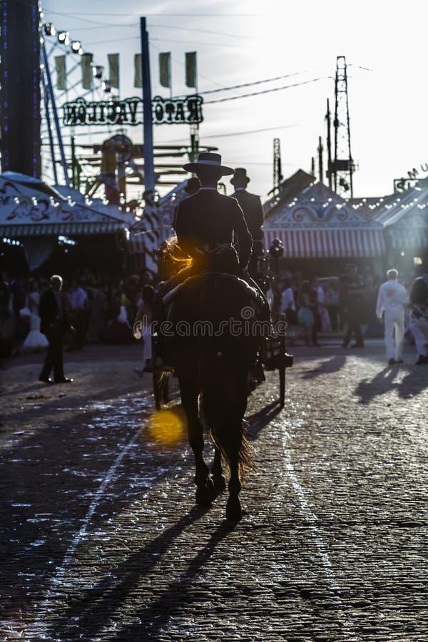 Silueta del jinete del caballo en la puesta del sol ` S April Fair de Sevilla imagenes de archivo