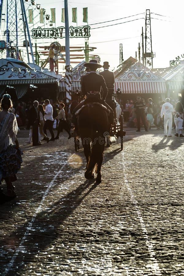 Silueta del jinete del caballo en la puesta del sol ` S April Fair de Sevilla imagen de archivo