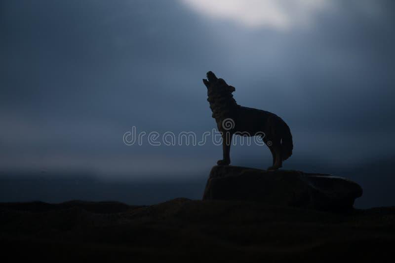 Silueta del lobo del grito contra fondo de niebla entonado oscuro Concepto del horror de V?spera de Todos los Santos imagen de archivo libre de regalías