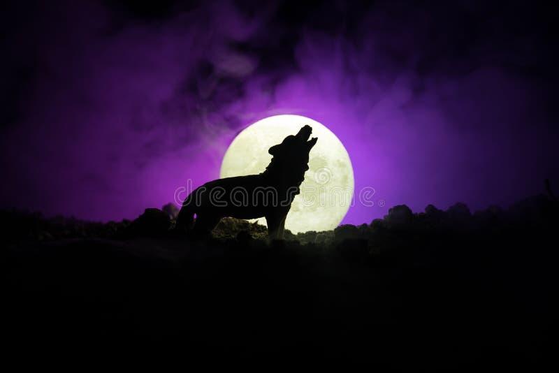 Silueta del lobo del grito contra fondo de niebla entonado oscuro y Luna Llena o lobo en silueta que gritan a la Luna Llena hola fotografía de archivo