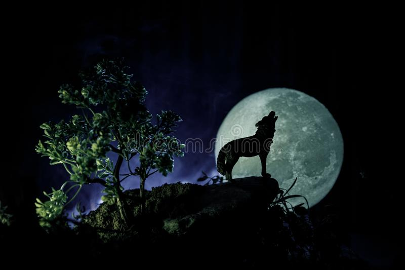 Silueta del lobo del grito contra fondo de niebla entonado oscuro y Luna Llena o lobo en silueta que gritan a la Luna Llena hola fotografía de archivo libre de regalías