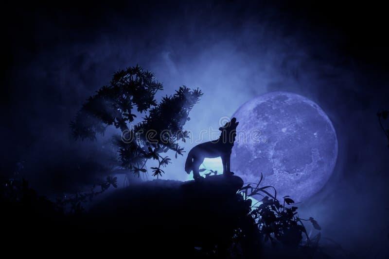 Silueta del lobo del grito contra fondo de niebla entonado oscuro y Luna Llena o lobo en silueta que gritan a la Luna Llena hola imagenes de archivo