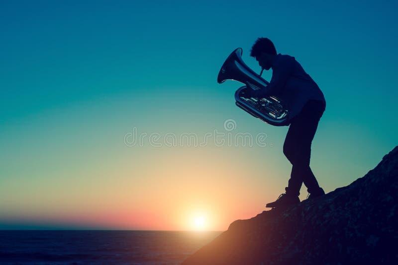 Silueta del músico que juega la tuba en costa de mar rocosa durante puesta del sol asombrosa imagenes de archivo