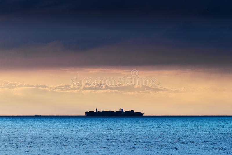 Silueta del mar Báltico grande de la travesía de portacontenedores bajo formación oscura dramática de la nube de nimboestrato imágenes de archivo libres de regalías