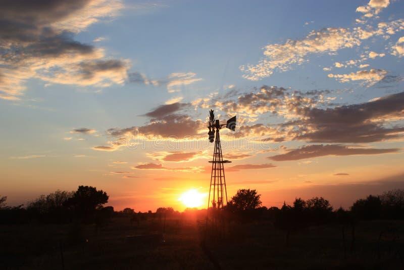 Silueta del molino de viento de Kansas con el cielo de oro fotografía de archivo