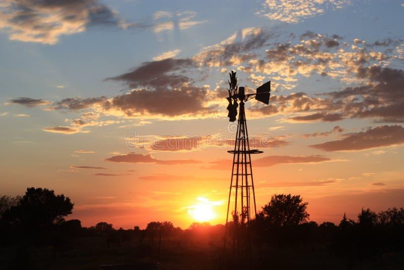 Silueta del molino de viento de Kansas con el cielo de oro imagen de archivo