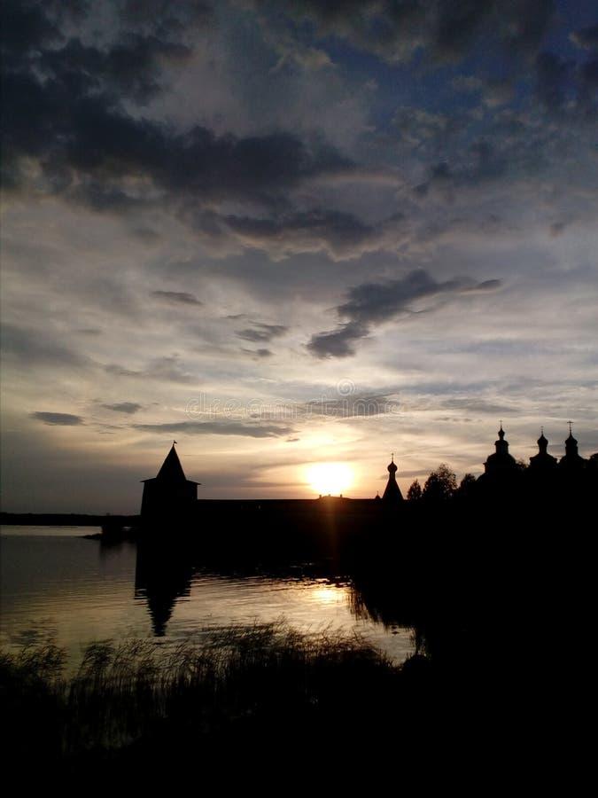 Silueta del monasterio, lago, cielo, puesta del sol imagen de archivo
