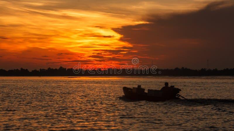 Silueta del montar a caballo del barco en la salida del sol de la mañana en el río de Hau, un distributary del río Mekong, Can Th foto de archivo libre de regalías