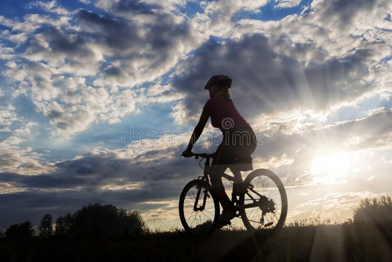 Silueta del montar a caballo del ciclista de la muchacha contra el cielo azul de la puesta del sol fotografía de archivo libre de regalías