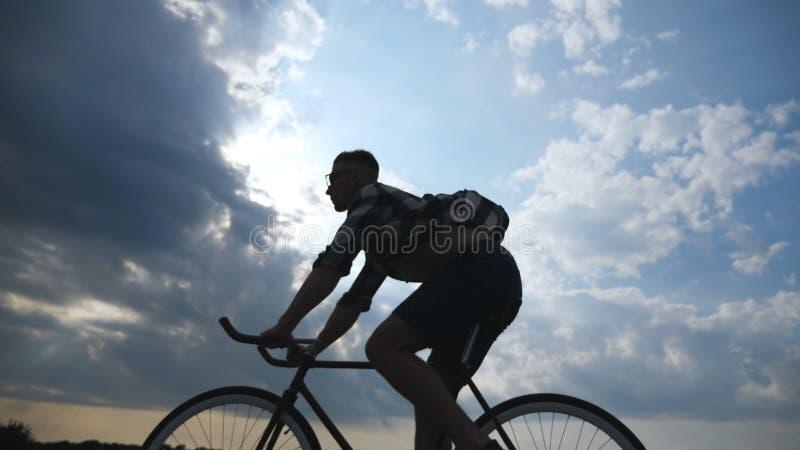 Silueta del montar a caballo del hombre joven en la bicicleta del vintage con el cielo hermoso de la puesta del sol en el fondo I imágenes de archivo libres de regalías