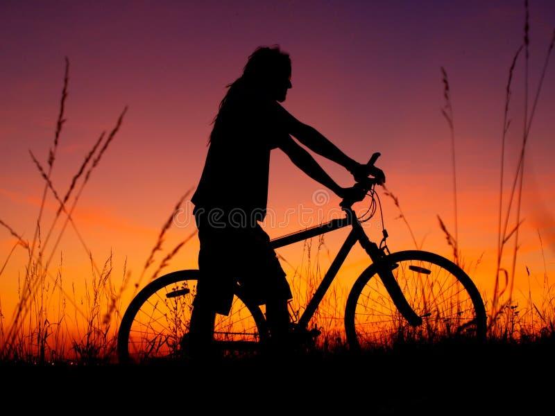 Silueta del motorista de la montaña en puesta del sol imagen de archivo