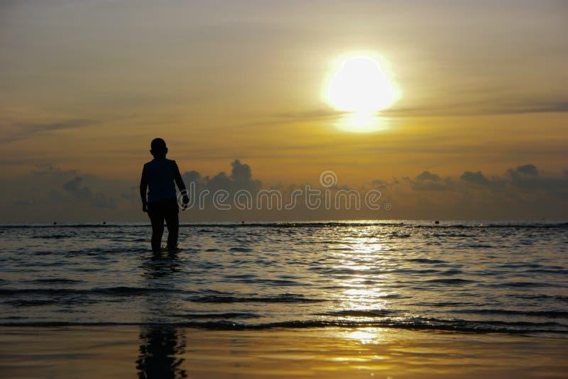 Silueta del muchacho asiático que se coloca en la playa durante beautif fotos de archivo