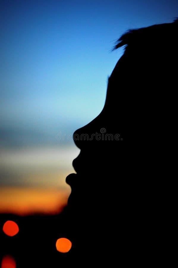 Silueta del muchacho que mira para arriba el cielo de la tarde imagen de archivo