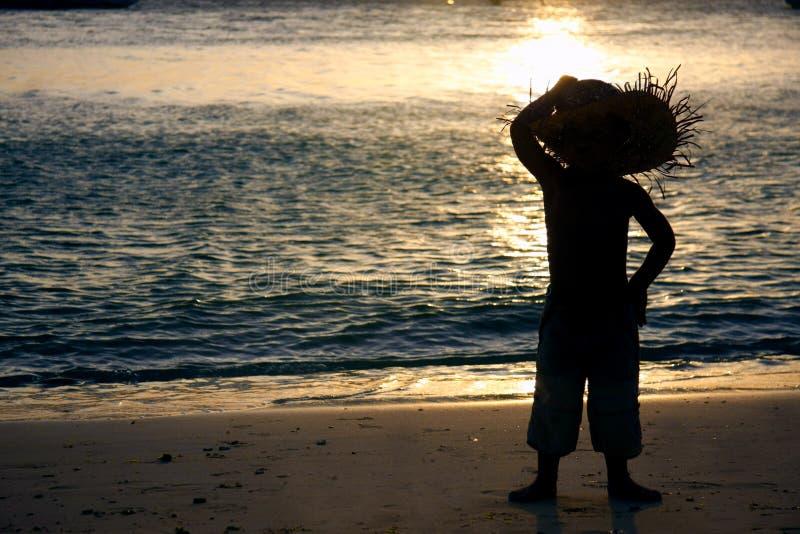 Silueta del niño en la playa que mira en el mar fotos de archivo libres de regalías