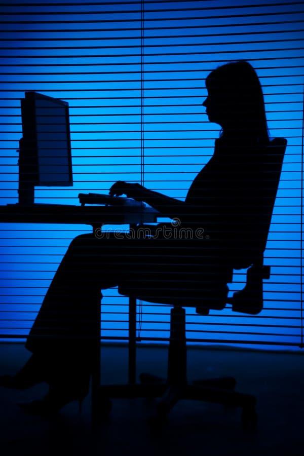 Silueta del ordenador de trabajo de la mujer (persianas) foto de archivo