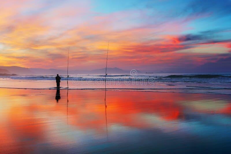 Silueta del pescador en la playa en la puesta del sol imagen de archivo