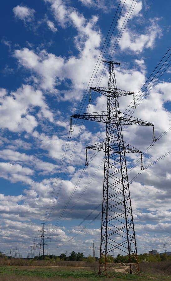 Silueta del pilón de la transmisión de la electricidad contra el cielo azul en la oscuridad imagen de archivo libre de regalías