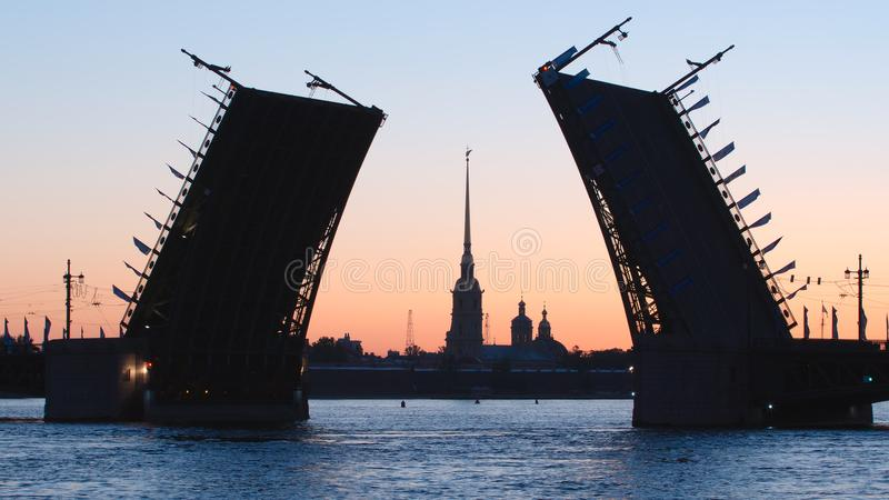 Silueta del puente abierto del palacio y capilla de la fortaleza por la mañana - St Petersburg, Rusia de Peter y de Paul fotografía de archivo