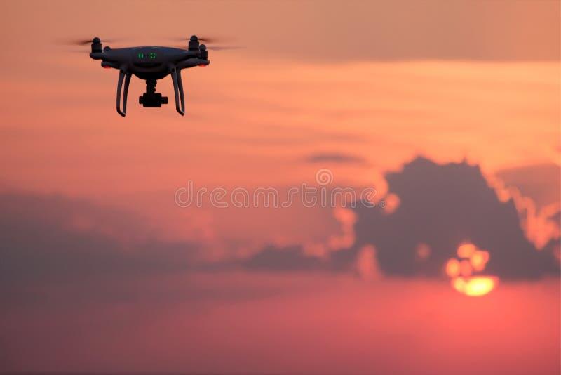 Silueta del quadrocopter contra el cielo con el sol poniente en la puesta del sol Un abejón se nubla la luz del sol Foto y vídeo  imágenes de archivo libres de regalías