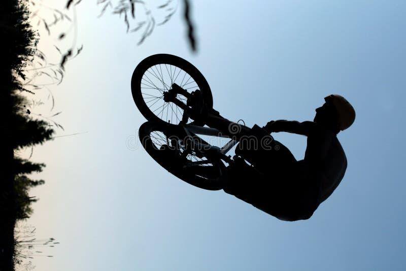 Silueta del salto de la bici imagenes de archivo