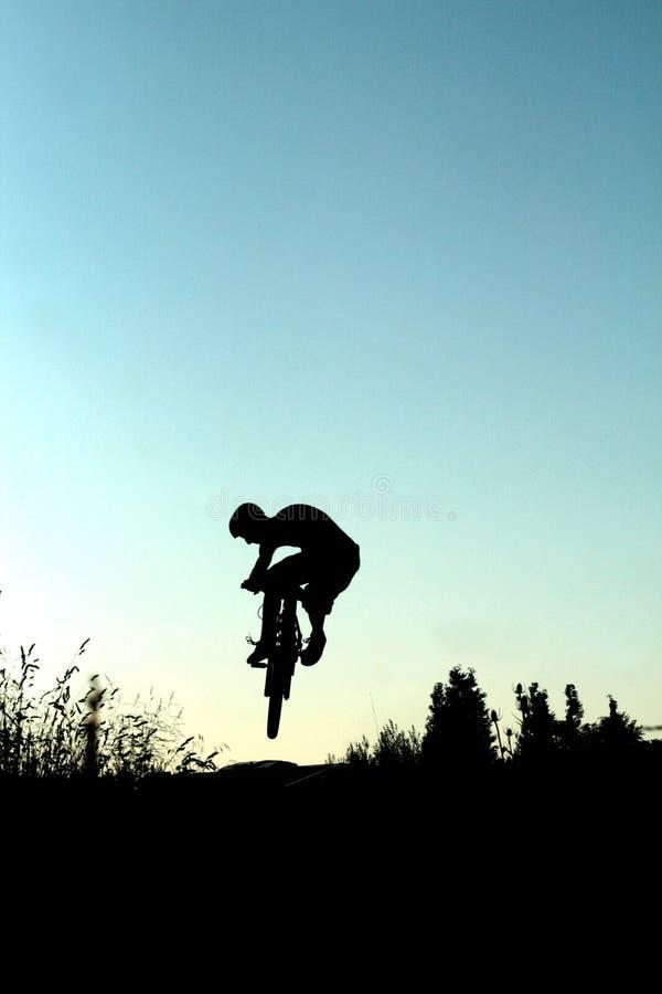 Silueta del salto de la bici imagen de archivo libre de regalías