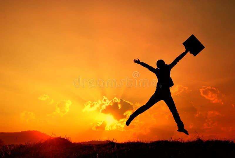 Silueta del salto y de la puesta del sol de la mujer de negocios foto de archivo