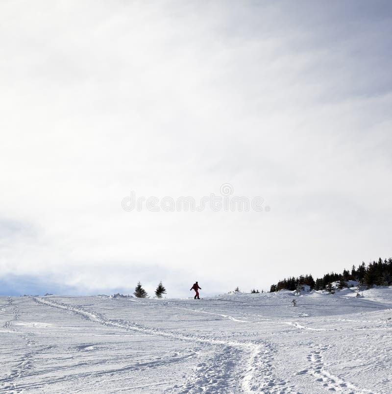 Silueta del snowboarder en declive en cuesta fuera de pista nevosa en w fotografía de archivo