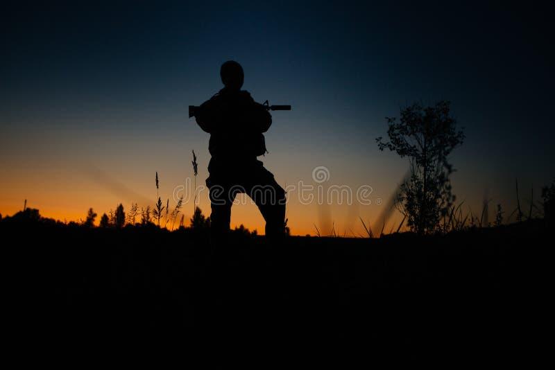 Silueta del soldado o del oficial militar con las armas en la noche imagenes de archivo